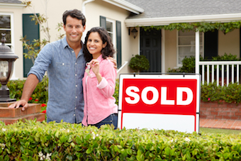 Couple standing beside a sold sign of a home with keys in hand